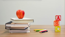 A red apple is balanced on top of some school books. Next to it on the right are some coloring pencils and A B C building blocks.